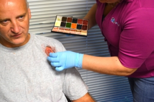 A SIMETRI employee applies makeup to simulate medical trauma.